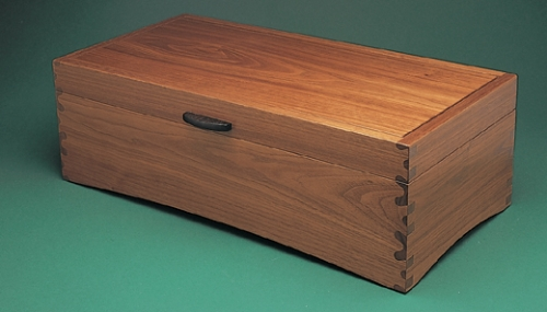 Storage Box in American black walnut with through Isoloc Bears Ears joint pattern. Handle in ebony. 5 1/2H x 16W x 8D