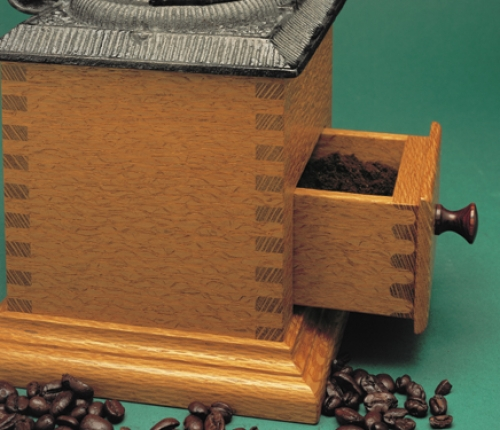 """Closeup of Coffee Grinder in lacewood with square finger joints and rounded half-blind finger joints on drawer. 10 1/4""""H x 6 1/2""""W x 6 1/2""""D"""